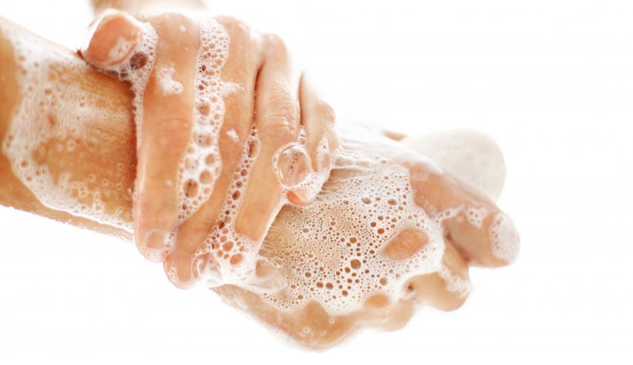 Side view of unrecognizable caucasian woman washing her hands with soap in bathroom.