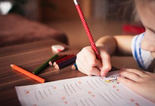 child in classroom writing
